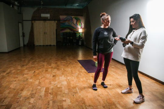 Brea Burke chats with Mandy Moreno about taking classes Friday, Jan. 18, 2019, at Yoga San Angelo.