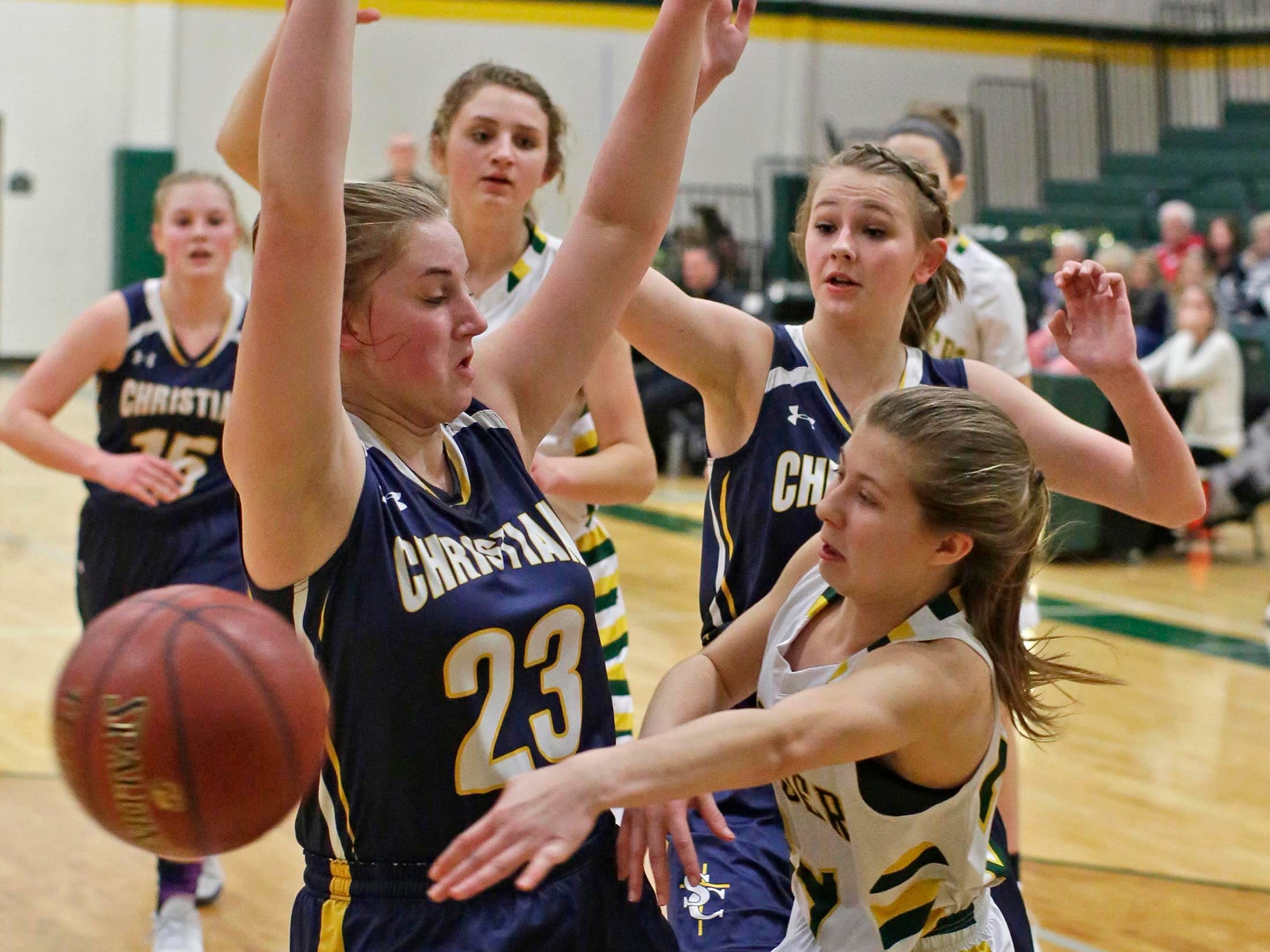 Sheboygan Lutheran's Hailey Schimberg (24) passes the ball by Sheboygan Christian's Olivia Heinen (23), Thursday, January 24, 2019, in Sheboygan, Wis.