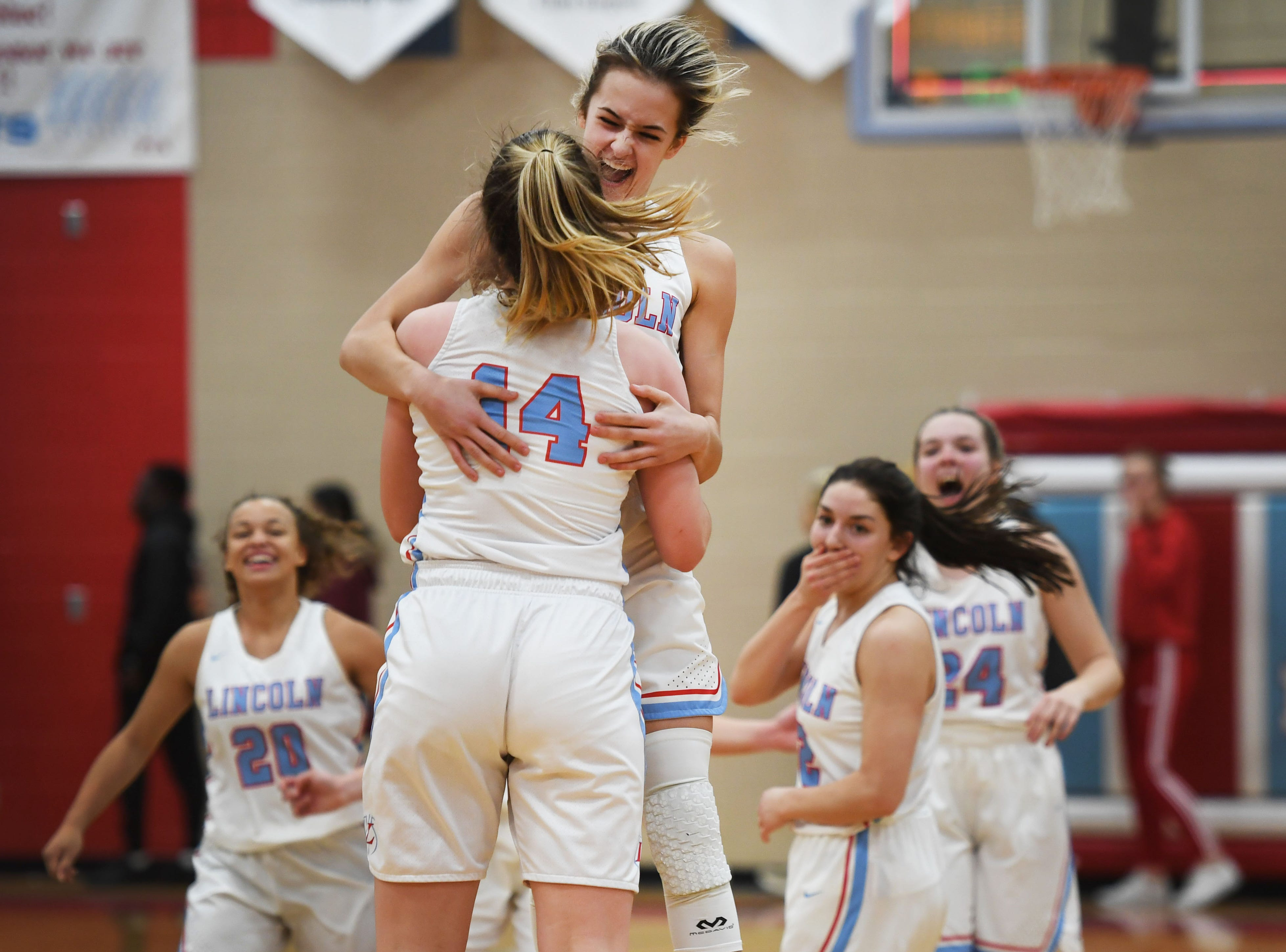 Lincoln celebrates around Emma Osmundson after she scores three points in the last seconds of the game against Washington Thursday, Jan. 24, at Lincoln. Lincoln won 63-62 against Washington.
