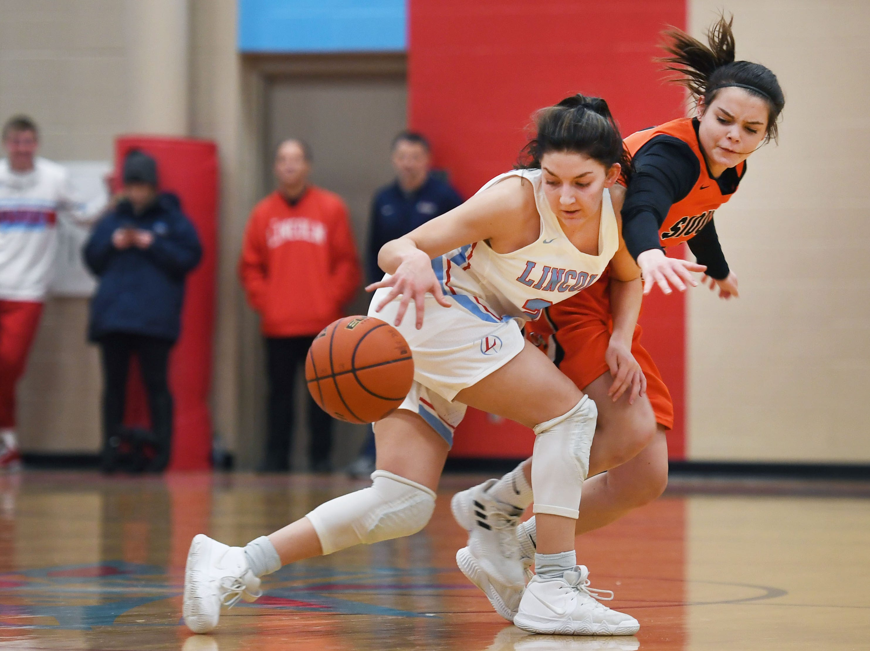 Lincoln's Brooke Brown gains control of the ball against Washington's Brynn Heinert during the game Thursday, Jan. 24, at Lincoln. Lincoln won 63-62 against Washington.