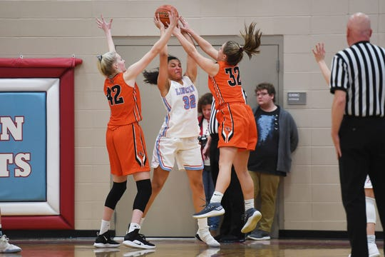 Lincoln's Sydnaya Dunn goes against Washington's Sydni Schetnan (42) and Peyton Rymerson (32) during the game Thursday, Jan. 24, at Lincoln. Lincoln won 63-62 against Washington.