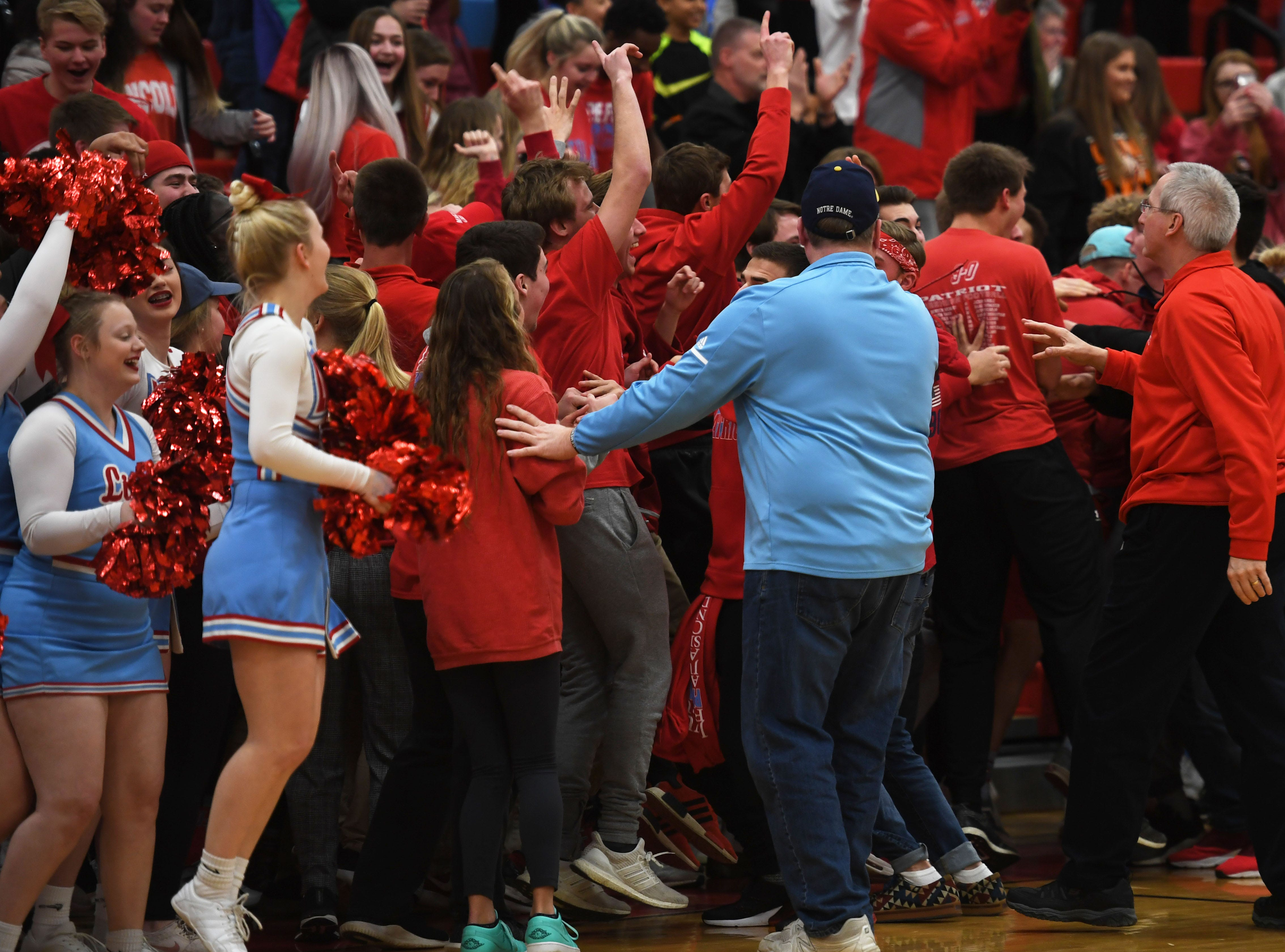 Lincoln teachers and staff attempt to keep the student section from rushing the court after Emma Osmundson scores three points in the last seconds of the game against Washington Thursday, Jan. 24, at Lincoln. Lincoln won 63-62 against Washington.
