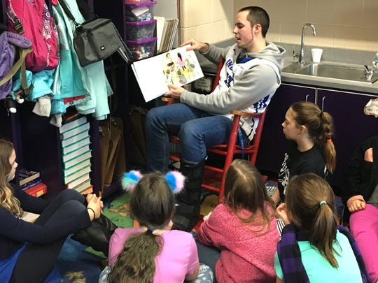 Bryce Owens, a Fort Defiance senior, reads to Clymore Elementary School students Thursday.