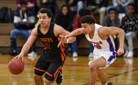 Tech's Kedrik Osourah advances with the ball against Lukas Theisen of Apollo during the Thursday, Jan 24, game at Tech High School in St. Cloud.