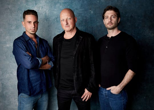 """Wade Robson, from left, director Dan Reed and James Safechuck pose for a portrait to promote the film """"Leaving Neverland"""" at the Salesforce Music Lodge during the Sundance Film Festival on Thursday, Jan. 24, 2019, in Park City, Utah. (Photo by Taylor Jewell/Invision/AP)"""