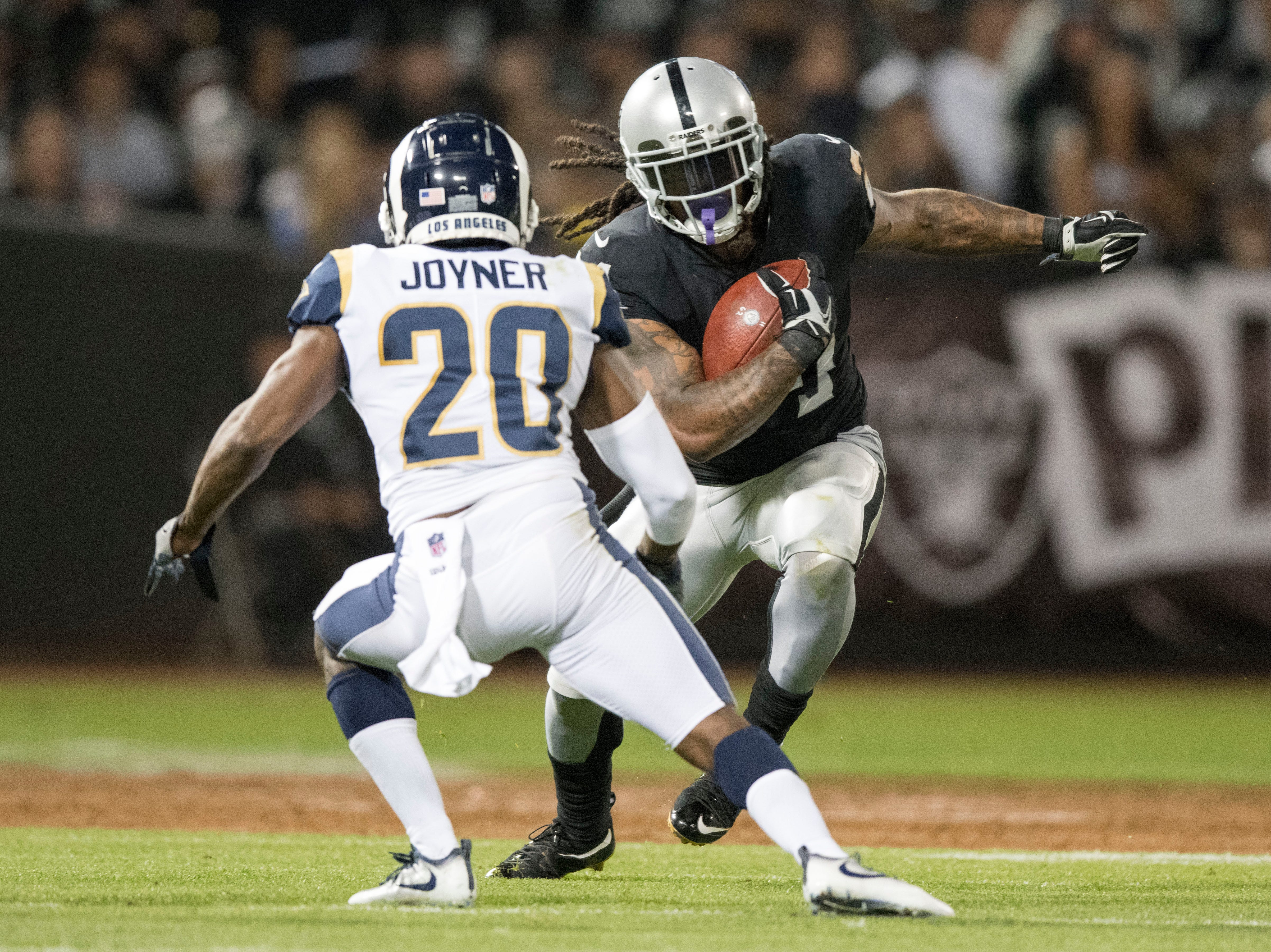 September 10, 2018; Oakland, CA, USA; Oakland Raiders running back Marshawn Lynch (24) runs the football against Los Angeles Rams safety Lamarcus Joyner (20) during the first quarter at Oakland Coliseum. Mandatory Credit: Kyle Terada-USA TODAY Sports
