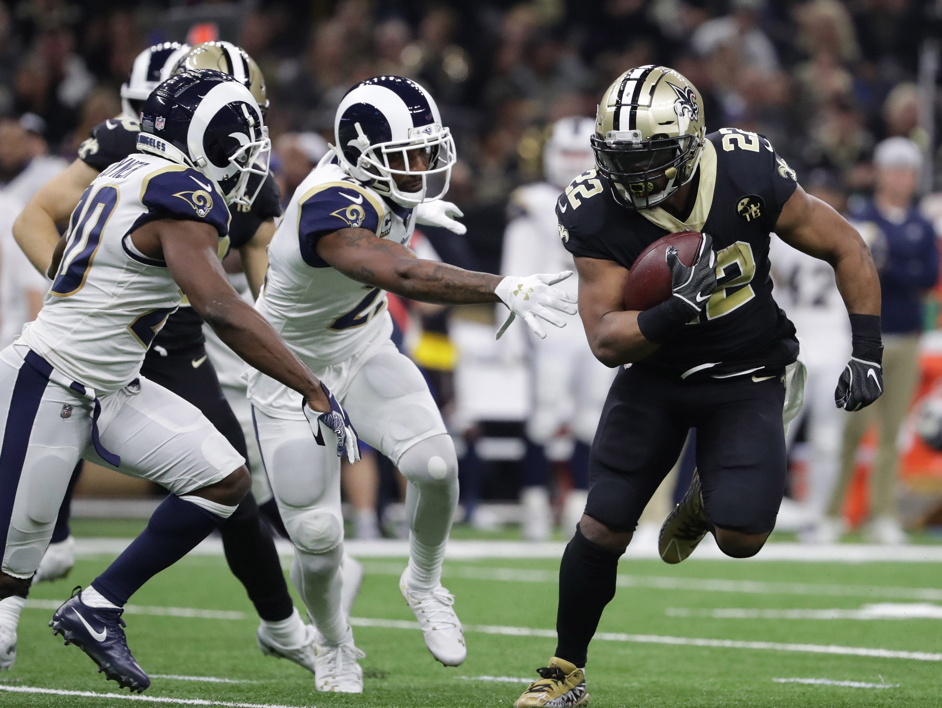 Jan 20, 2019; New Orleans, LA, USA; New Orleans Saints running back Mark Ingram (22) runs the ball against Los Angeles Rams free safety Lamarcus Joyner (20) and cornerback Aqib Talib (21) during the third quarter of the NFC Championship game at Mercedes-Benz Superdome. Mandatory Credit: Derick E. Hingle-USA TODAY Sports
