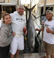 Newlyweds Brooke and Michael Hayes of Chesterton, Ind., left, celebrate with mate Troy McDonald of Happy Day Today charters after Hayes caught a pending world record 97.8-pound kingfish.