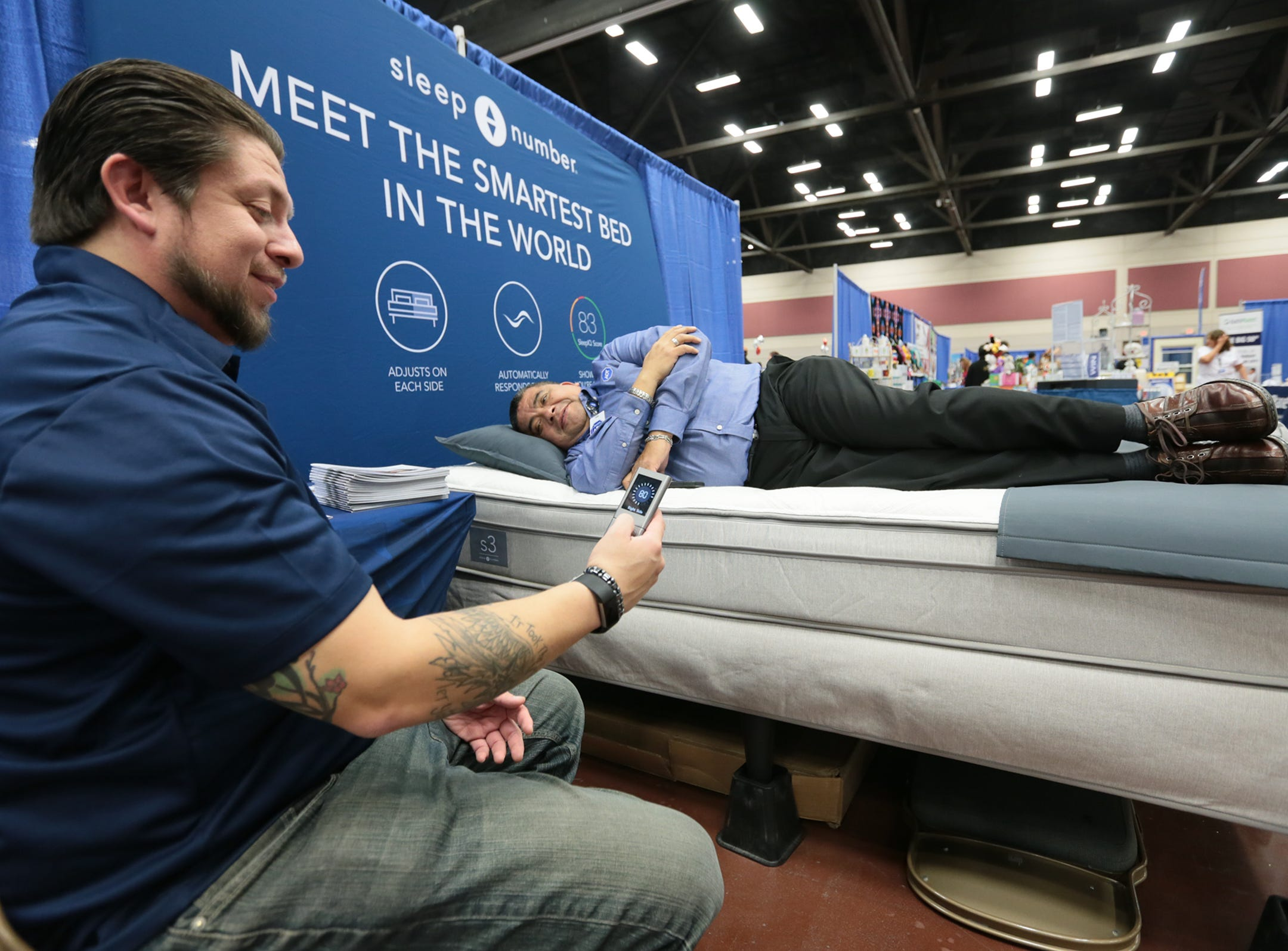 Juan Castillo demonstrates a Sleep Number bed for Jerry Araiza Friday at the El Paso Spring Home Show and Pet Expo.