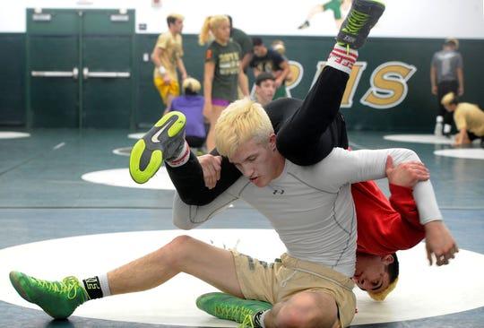 Jacob Hansen flips teammate Arshag Dadourian during Royal 's wrestling practice Thursday.