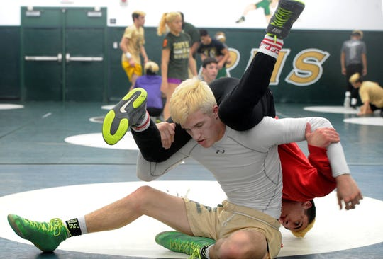 Jacob Hansen flips teammate Arshag Dadourian during Royal 's wrestling practice Thursday.