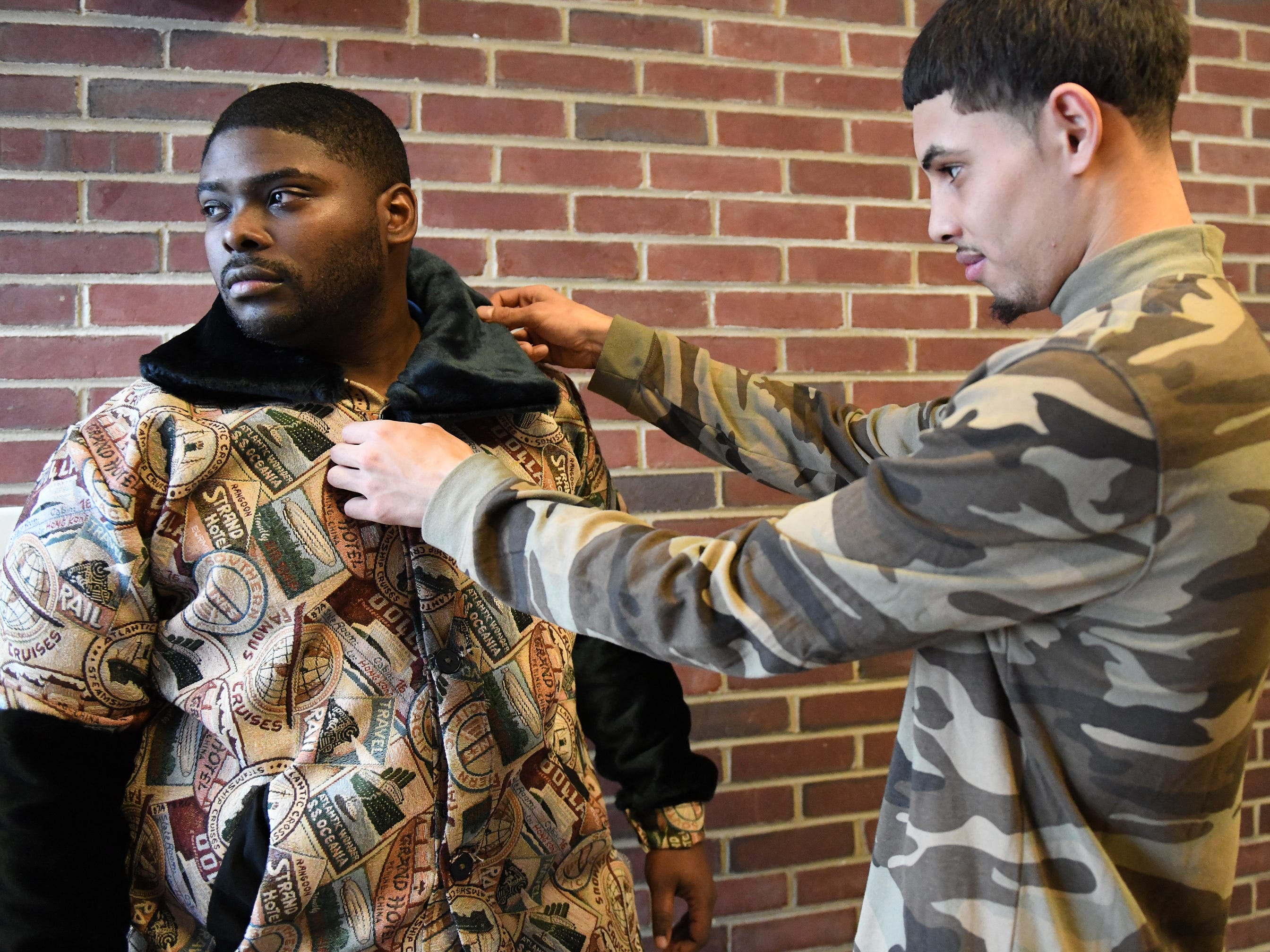 Fabricio Lobo (right) adjusts the collar on a coat he designed while Cunningham Academy staffer Zaquiiran Jones helps show off the garment on Thursday, Jan. 24, 2019.
