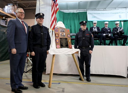 Probationary Firefighters Sean Hatfield from the LaGrange fire department and Daniel Costa from the New Rochelle fire department, present their class plaque to John, M. Cullen, the Westchester County Department of Emergency Services commissioner, during the Class 02-2018 graduation from the Westchester County Career Chiefs Fire Academy at the Support Services Building at the Department of Emergency Services in Valhalla, Jan. 25, 2019. The new firefighters are from Eastchester, Fairview, New Rochelle, Scarsdale and White Plains. Dutchess County also graduated firefighters from Arlington, LaGrange, and Middletown.