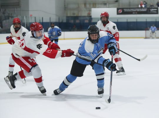 Suffern center Tommy McCarren (10) works the puck past North Rockland forward Aiden Grange (19) during varsity ice hockey action at Sport-O-Rama Ice Rink in Monsey on Friday, January 25, 2019.
