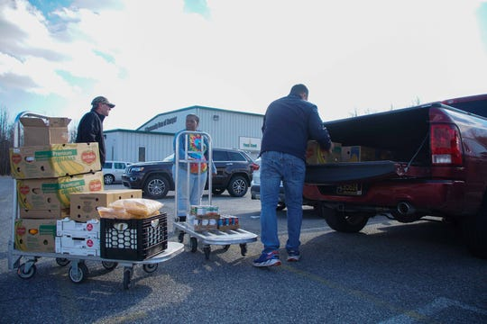 Stephen, 37, a furlough government worker, loads food into his truck that is being distributed by the Food Bank of Delaware in Milford government workers affected by the shutdown.