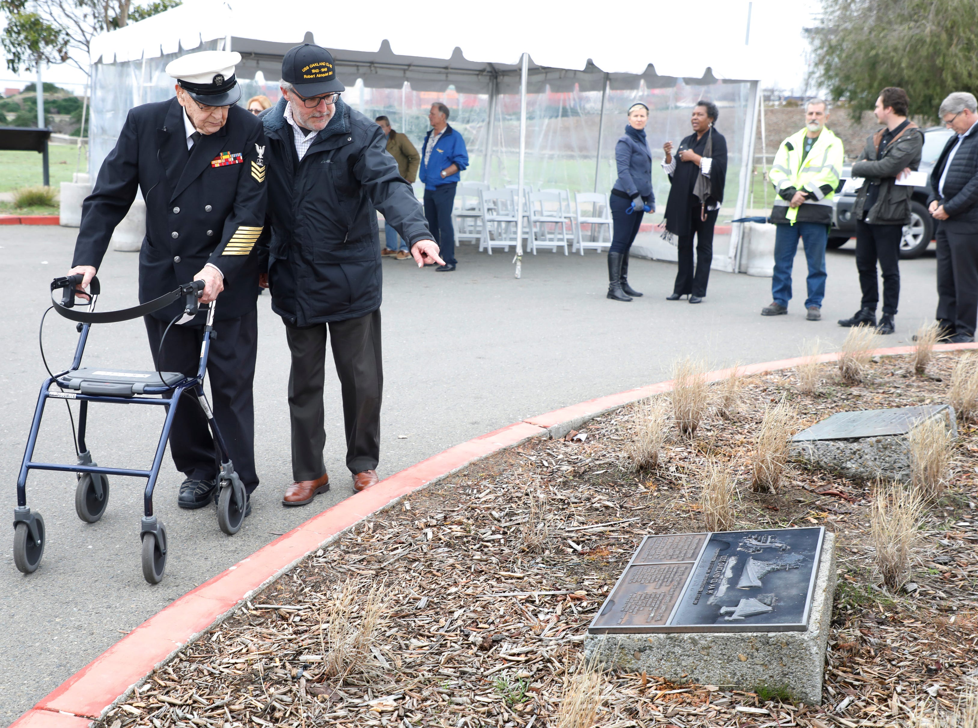 Paul Ferreira, right, points out a plaque at the base of the USS Oakland mast to WWII veteran Robert Almquist, 95, who traveled from Wisconsin to see the last remaining piece of the ship he served on at Middle Harbor Shoreline Park in Oakland, Calif., on Friday, Jan. 11, 2019. The Almquist family had raised money on a GoFundMe page to bring the World War II Navy veteran to the West Coast,  to visit the mast and to see a plaque bearing his name at the Mt. Soledad National Veterans Memorial in La Jolla.  Visit Oakland heard about the fund raising and decided to pay for Almquist's flight to Oakland. (Laura A. Oda/Bay Area News Group)