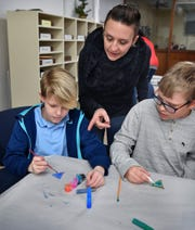 Teaching artist Amber Day Scott works with Olney Elementary fifth graders Jason Graha, left, and Rowland Scott as they paint plexiglas keychain fobs Friday at the Times Record News.