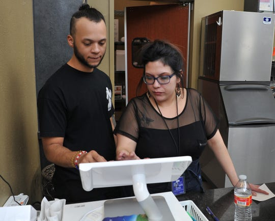 Southern Girls Kitchen Manager, Eric Luster, left, and Operations Coordinator, Courtney Ragsdale work the register of their restaurant, located in the Wichita Falls Reginal Airport, Friday afternoon. The restaurant announced they would give free hamburgers to furloughed employees.