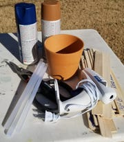 To make a bushel basket using painted sticks, the material needed includes: paint sticks, small clay pot,  heavy duty scissors or tin snips, glue gun, spray paint and various embellishments.
