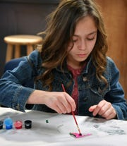 Taylor Lawrence paints a plexiglas triangle for a keychain after a visit to the Wichita Dome art installation with her Olney Elementary classmates Friday. The Wichita Dome is a geodesic structure made of painted plexiglas panels.