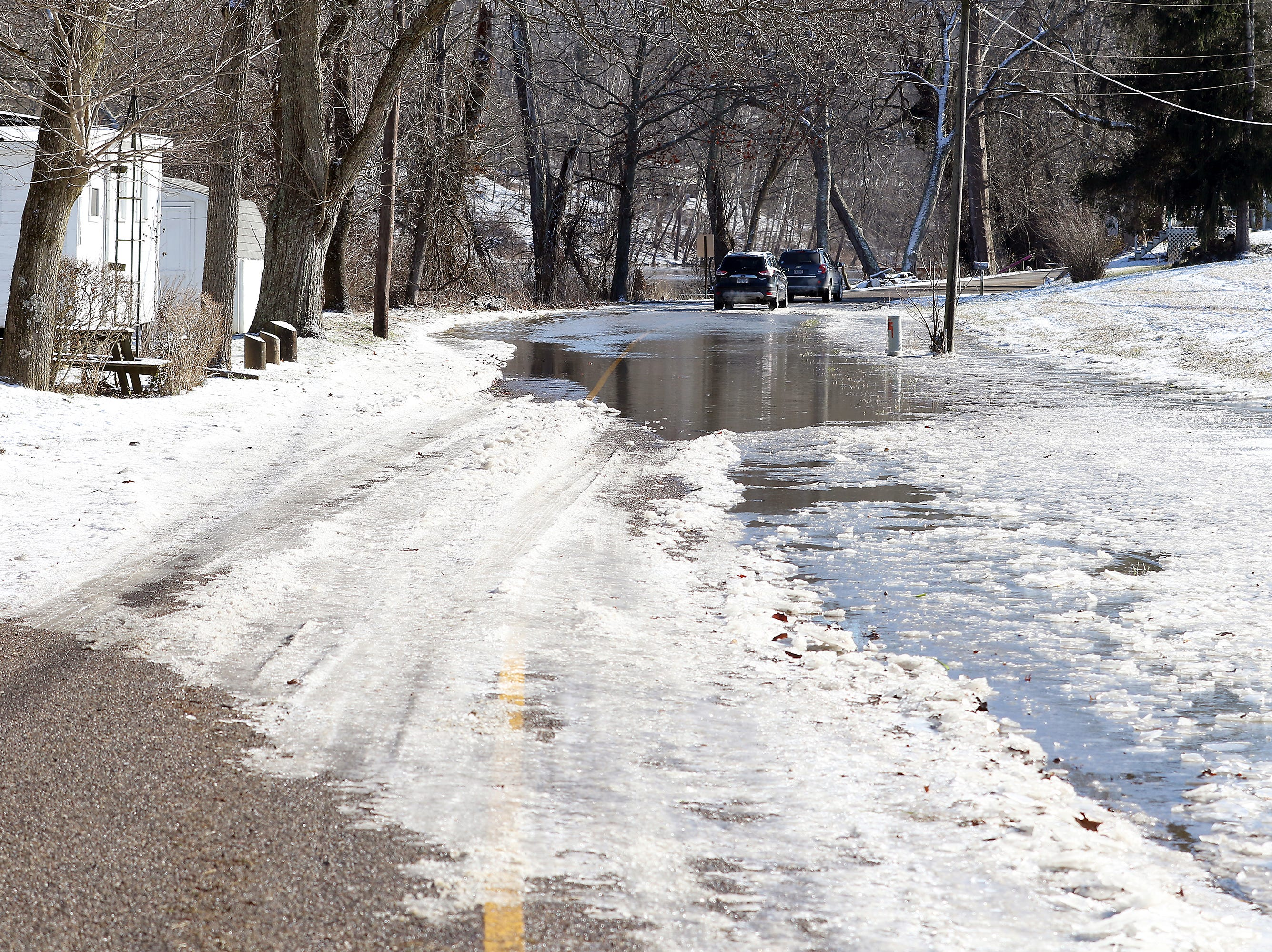 Mostly-frozen water covers Old River Road south of Gaysport Friday afternoon.