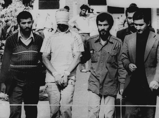 In this Nov. 9, 1979 file photograph, one of the American hostages seized when Islamic radicals stormed the U.S. Embassy in Tehran, is seen blindfolded and with his hands bound, in Tehran.