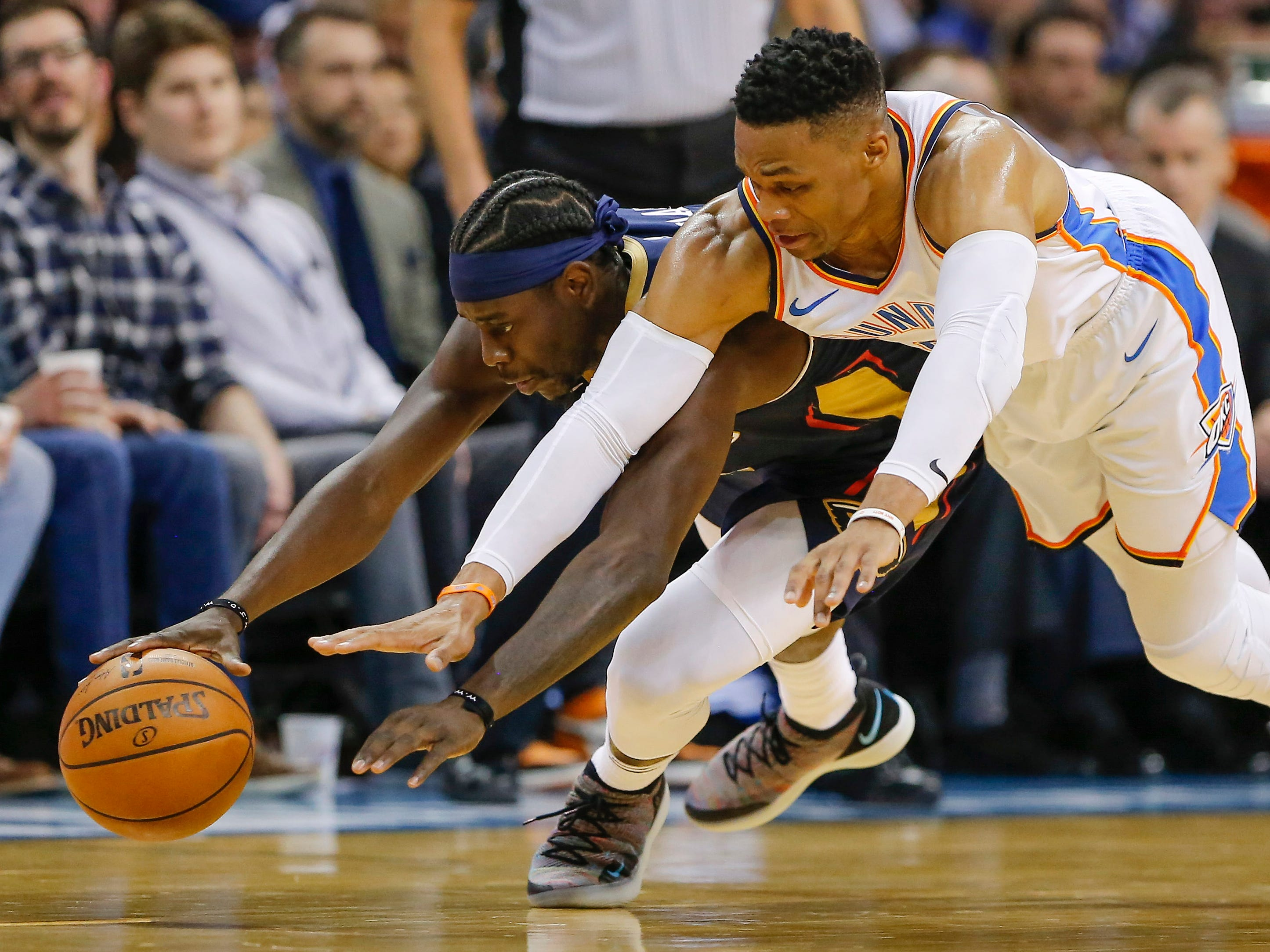 Jan. 24: Pelicans guard Jrue Holiday, left, and Thunder guard Russell Westbrook hit the deck while scrambling for a loose ball during the second half in Oklahoma City.