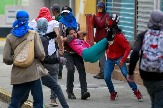 Several people help a young woman after fainting from inhaling tear gas, Wednesday, during a protest against the Government of the Venezuela President Nicolas Maduro. Thousands demonstrated  in the 23 states of the country and the Capital District against Nicolas Maduro.