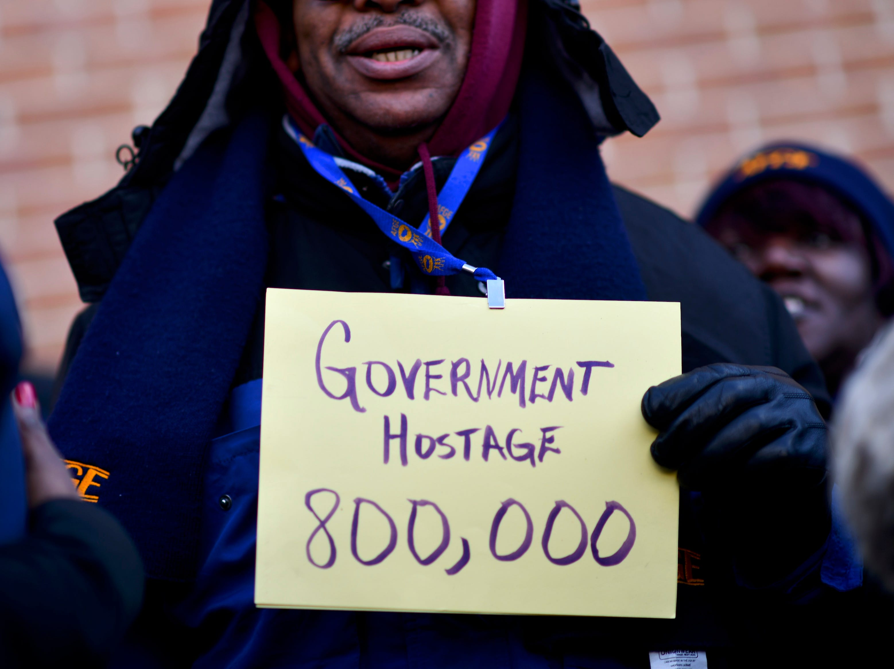 A protester holds a placard while demonstrating with Philadelphia Airport TSA and airport workers outside the Philadelphia International Airport on Jan. 25, 2019 in Philadelphia, Pa.
