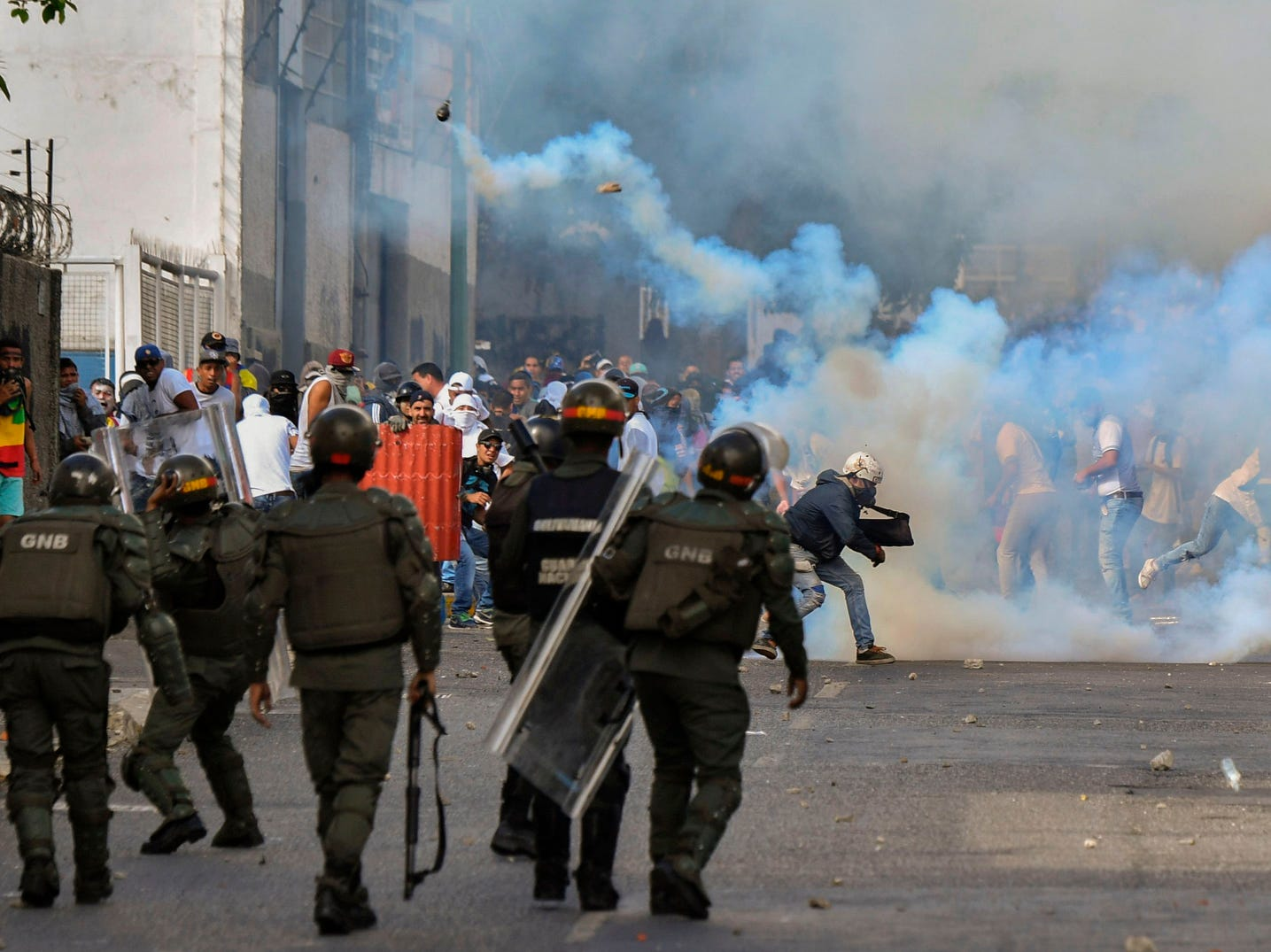 Opposition demonstrators clash with security forces, Wednesday, during a protest against the government of President Nicolas Maduro on the anniversary of the 1958 uprising that overthrew the military dictatorship, in Caracas, Venezuela.