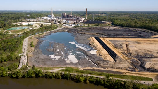 FILE - In this his May 1, 2018, file photo, the Richmond, Va., city skyline is seen in the horizon behind the coal ash ponds along the James River near Dominion Energy's Chesterfield Power Station in Chester, Va. The Virginia General Assembly has reached a bipartisan agreement on a bill that would clean up large coal ash ponds across the state. (AP Photo/Steve Helber, File)