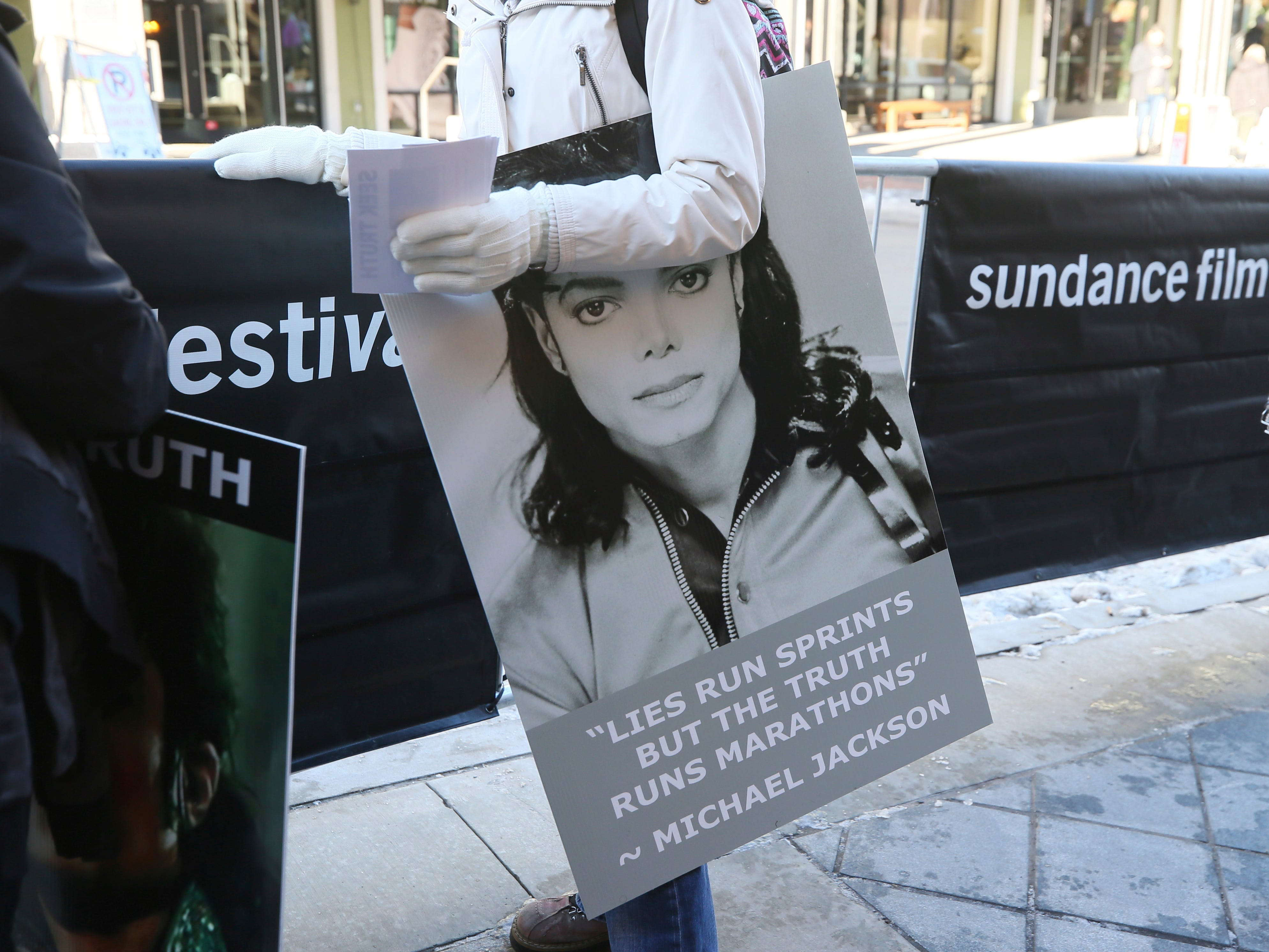 Eine Frau, die aus Calgary, Kanada, gefahren ist, hält ein Zeichen der Unterstützung für Michael Jackson außerhalb der Premiere von