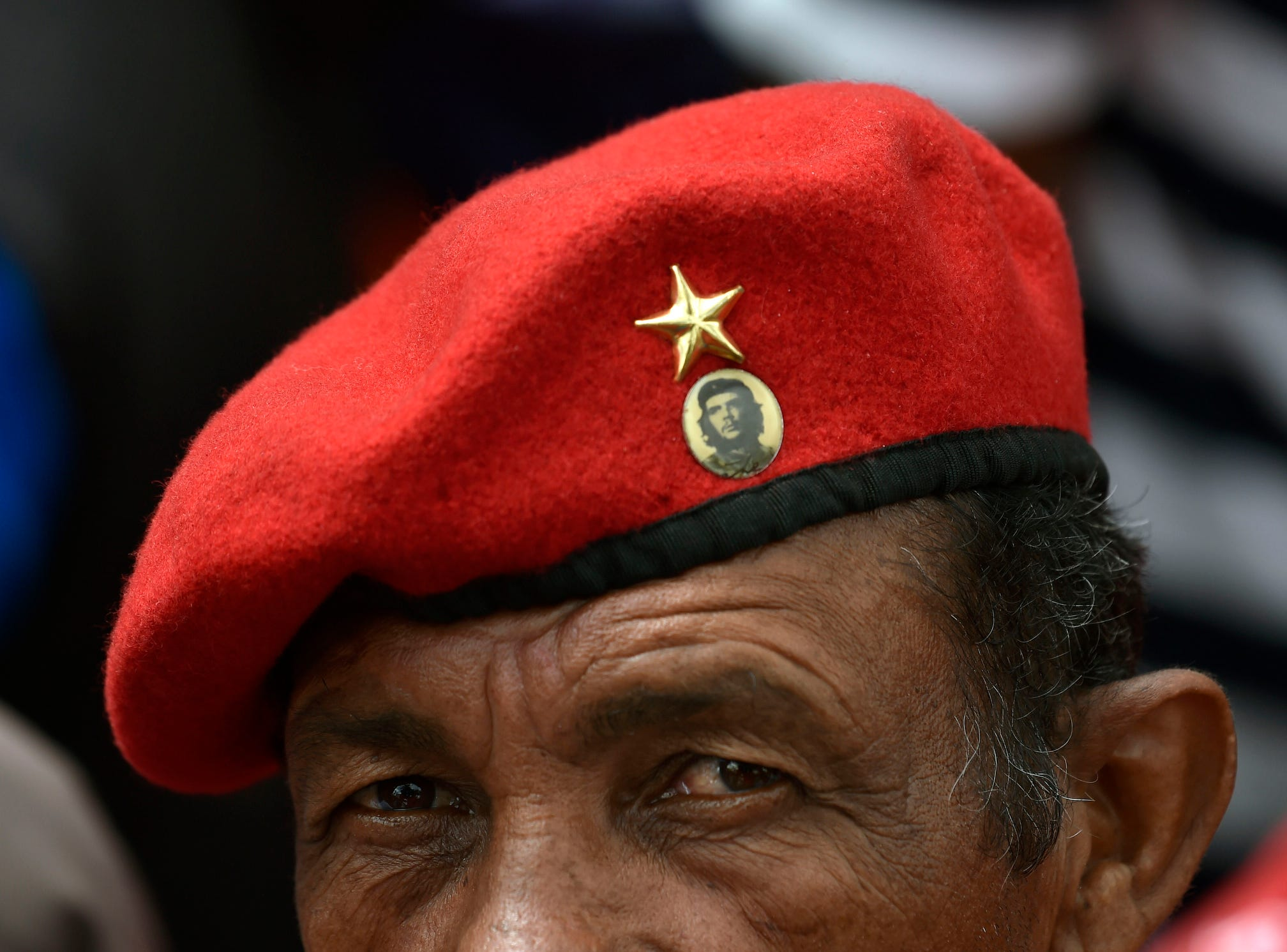"A supporter of President Nicolas Maduro's government  wears a beret with a button depicting Argentine-born revolutionary leader Ernesto ""Che"" Guevara , while taking part in a march, on the anniversary of 1958 uprising that overthrew military dictatorship in Caracas."