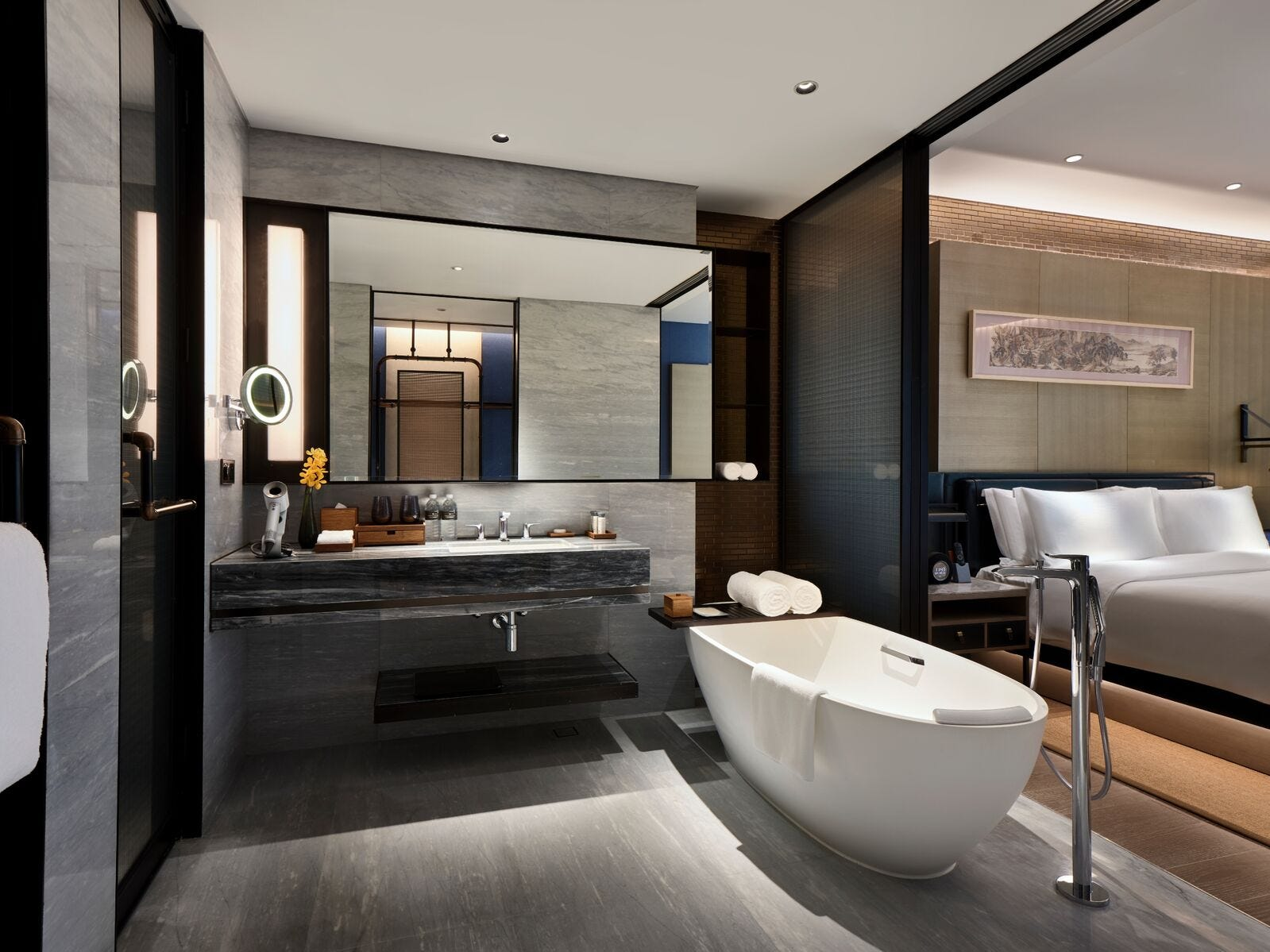 Some rooms have open-plan bathrooms with sliding doors for privacy while others, like this suite bathroom, have fanciful vanities and lighting fixtures. Guest rooms stock Salvatore Ferragamo products while suites pile on the luxury with Acqua di Parma goodies.