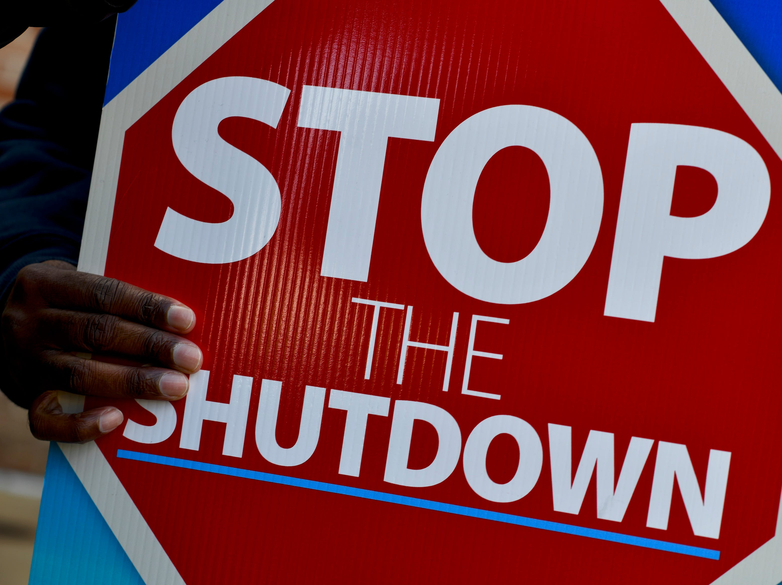"A protestor holds a placard stating ""STOP THE SHUTDOWN"" while demonstrating with Philadelphia Airport TSA and airport workers outside the Philadelphia International Airport on Jan. 25, 2019 in Philadelphia, Pennsylvania."