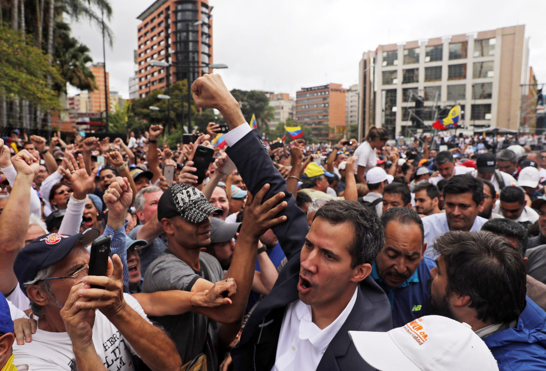 Juan Guaido (C), President of the Venezuelan Parliament, greets the crowd announcing that he assumes executive powers, in Caracas, Venezuela, on Wednesday.