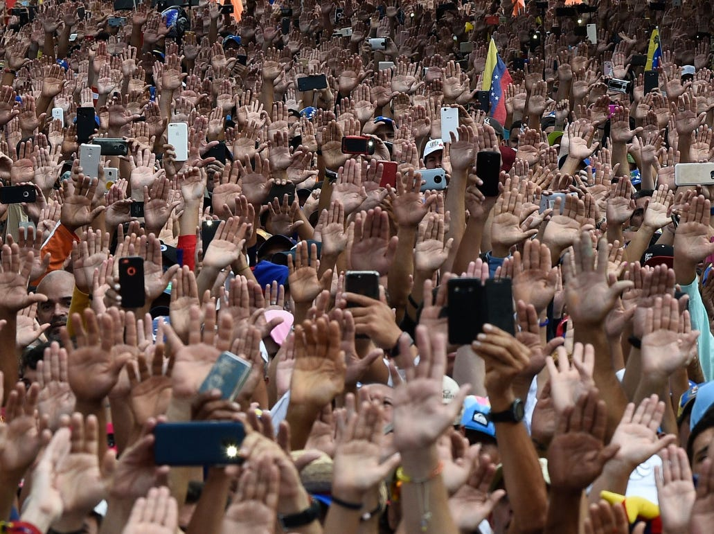 People raise their hands during a mass opposition rally against President Nicolas Maduro on the anniversary of a 1958 uprising that overthrew a military dictatorship, in Caracas on Jan. 23, 2019.