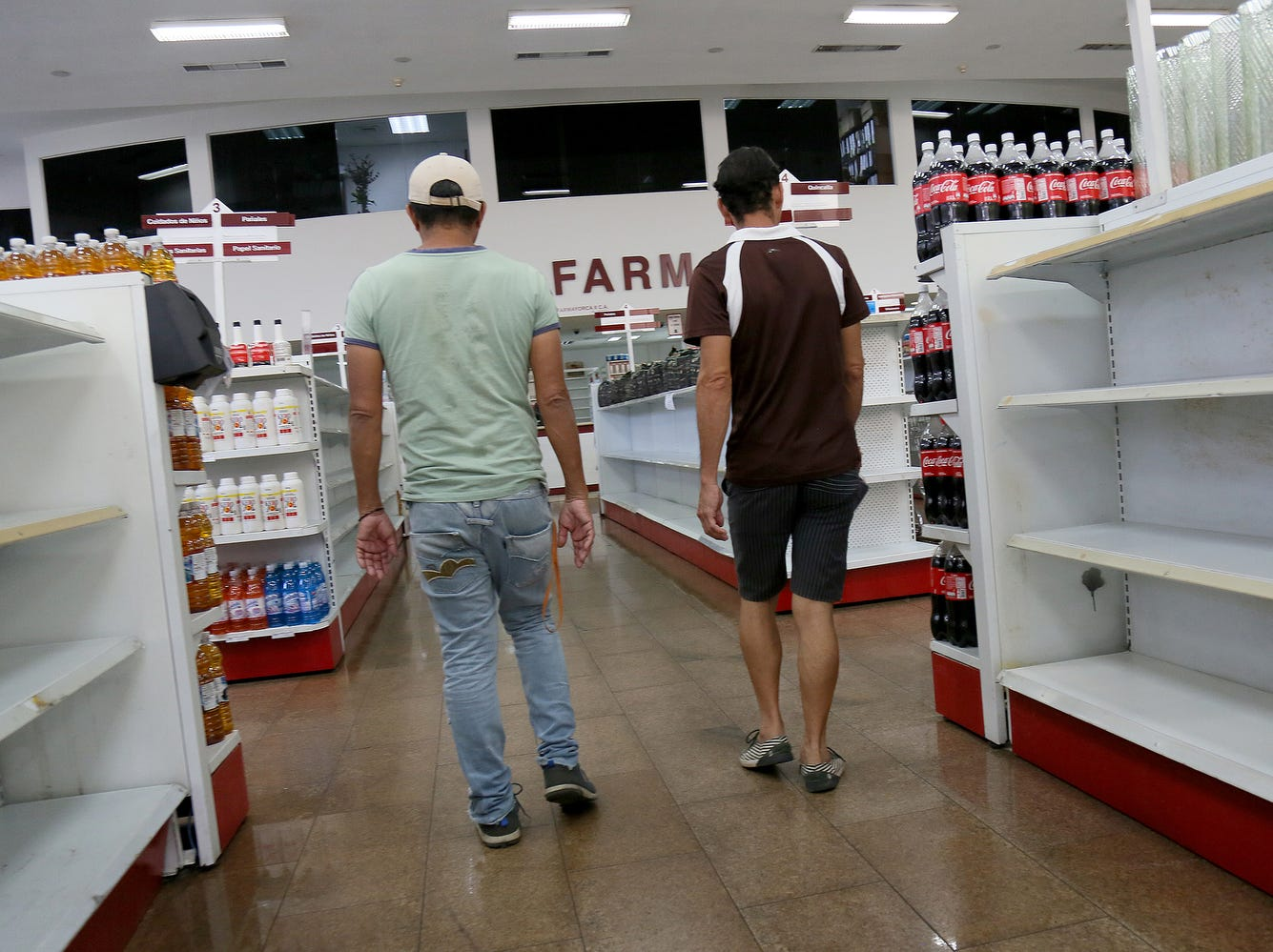 Two men looks for goods in a supermarket as some shelves look empty in the Petare district in Caracas, Venezuela.
