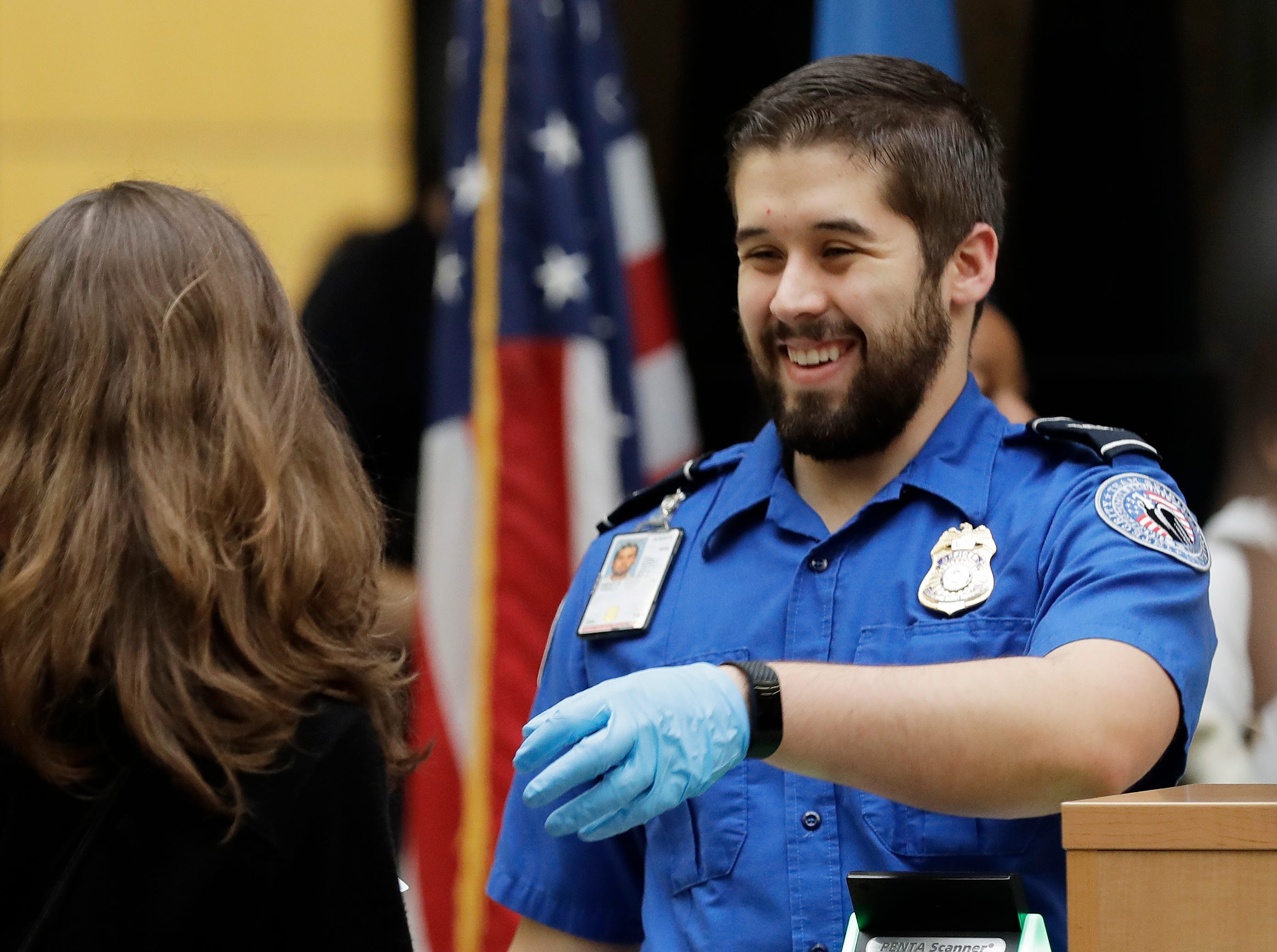 A TSA worker smiles as he checks travelers' boarding passes and identification, Friday, Jan. 25, 2019, at Seattle-Tacoma International Airport in Seattle. Yielding to mounting pressure and growing disruption, President Donald Trump and congressional leaders on Friday reached a short-term deal to reopen the government for three weeks while negotiations continue over the president's demands for money to build his long-promised wall at the U.S.-Mexico border.