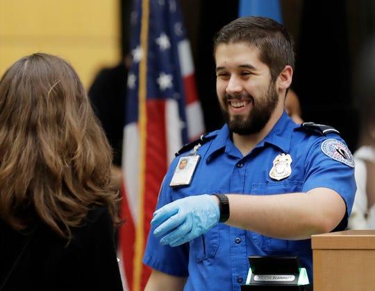 A TSA worker checks travelers' boarding passes and identification on Jan. 25, 2019, at Seattle-Tacoma International Airport.