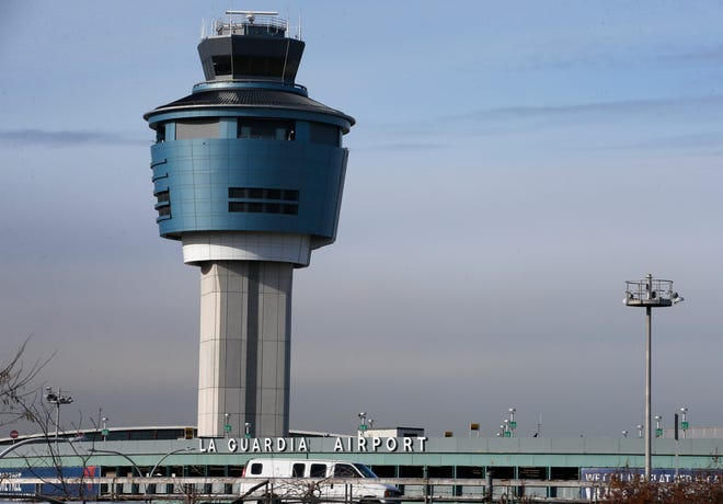 An air traffic control tower rises above a ramp serving LaGuardia Airport in New York on Jan. 21, 2015.