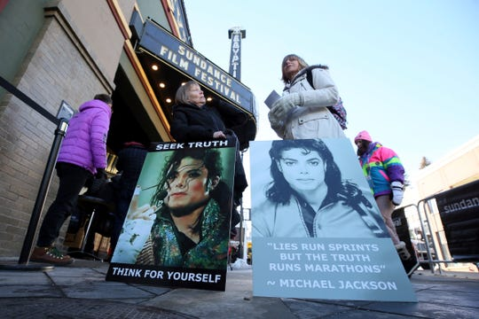 "Brenda Jenkyns, left, and Catherine Van Tighem, who drove from Calgary, Canada, stand with signs outside of the premiere of ""Leaving Neverland"" at Sundance Film Festival."