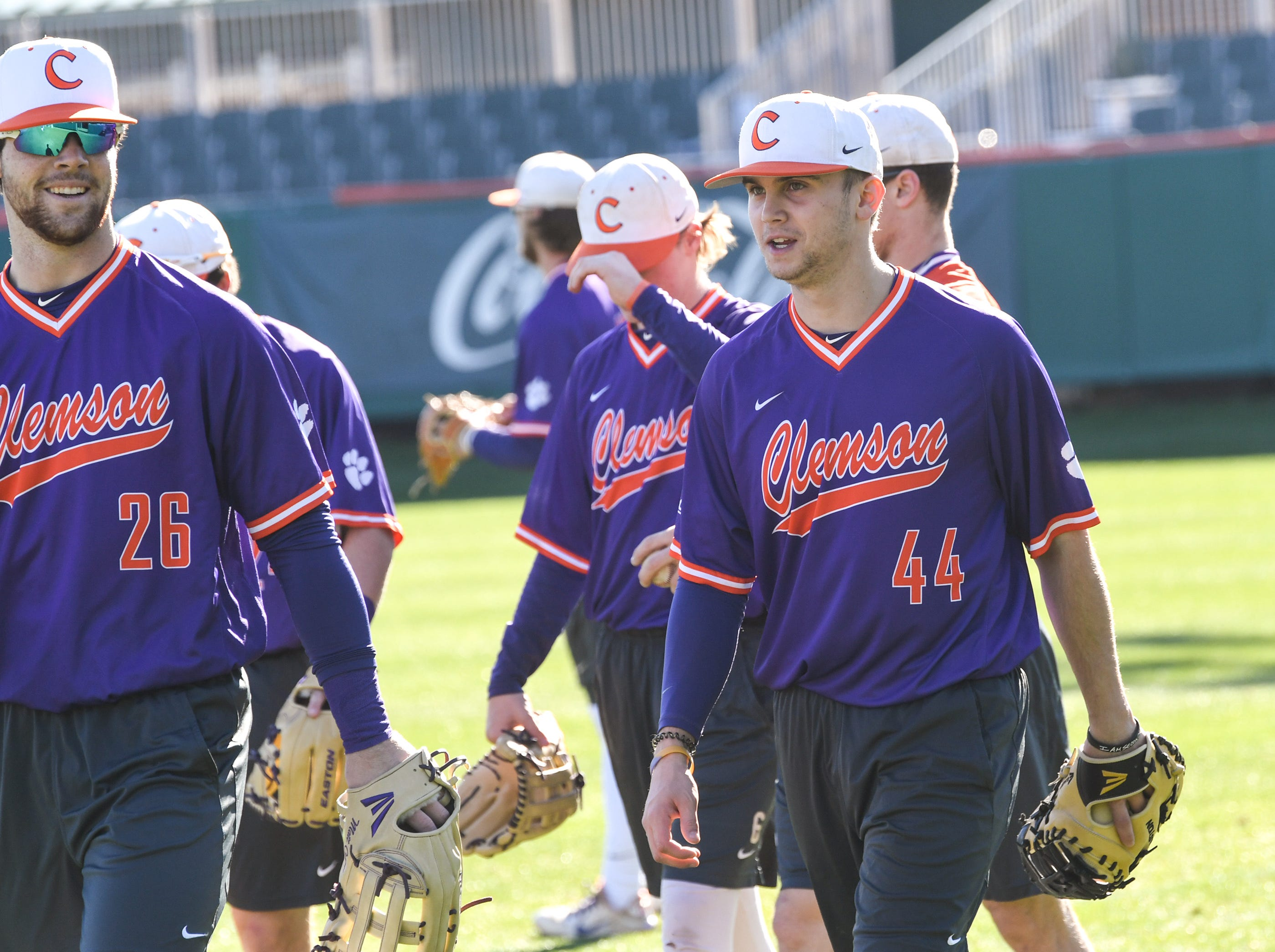 Clemson freshmen Matt Cooper (26), and Bryar Hawkins (44) warm up together during practice at Doug Kingsmore Stadium in Clemson Friday.