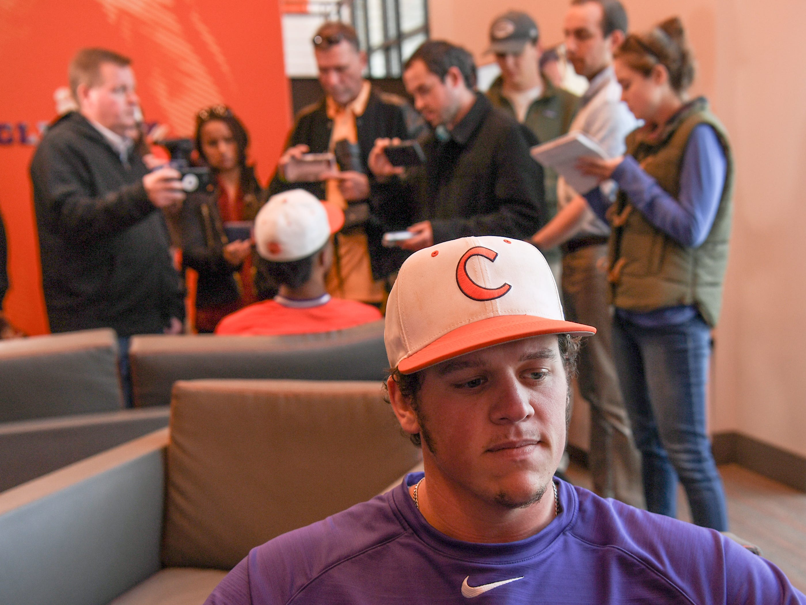Clemson pitcher Jacob Hennessy is interviewed while teammate Jordan Greene is by others before practice at Doug Kingsmore Stadium in Clemson Friday.