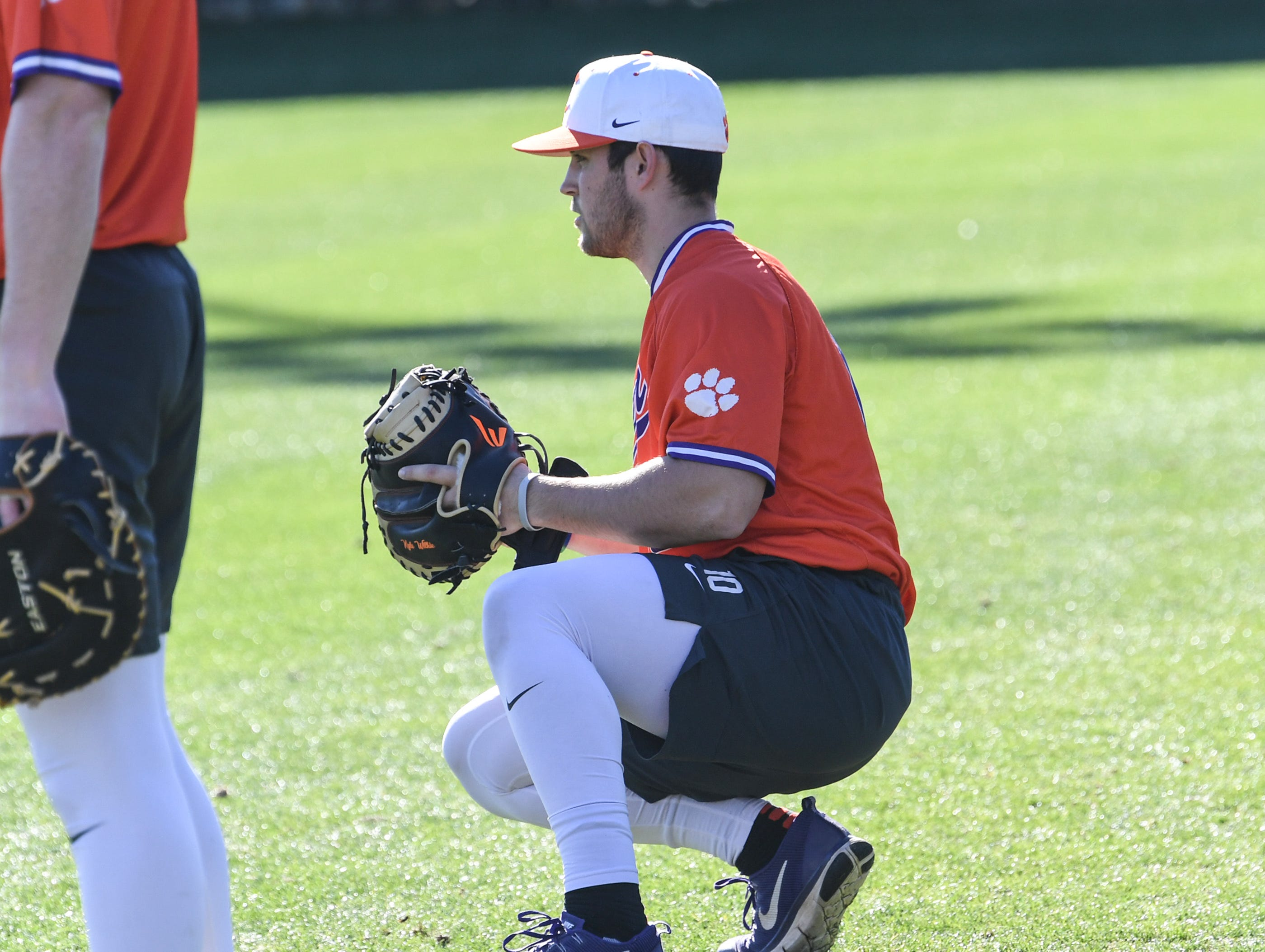 Clemson catcher Kyle Wilkie warms up with teammates during practice at Doug Kingsmore Stadium in Clemson Friday.