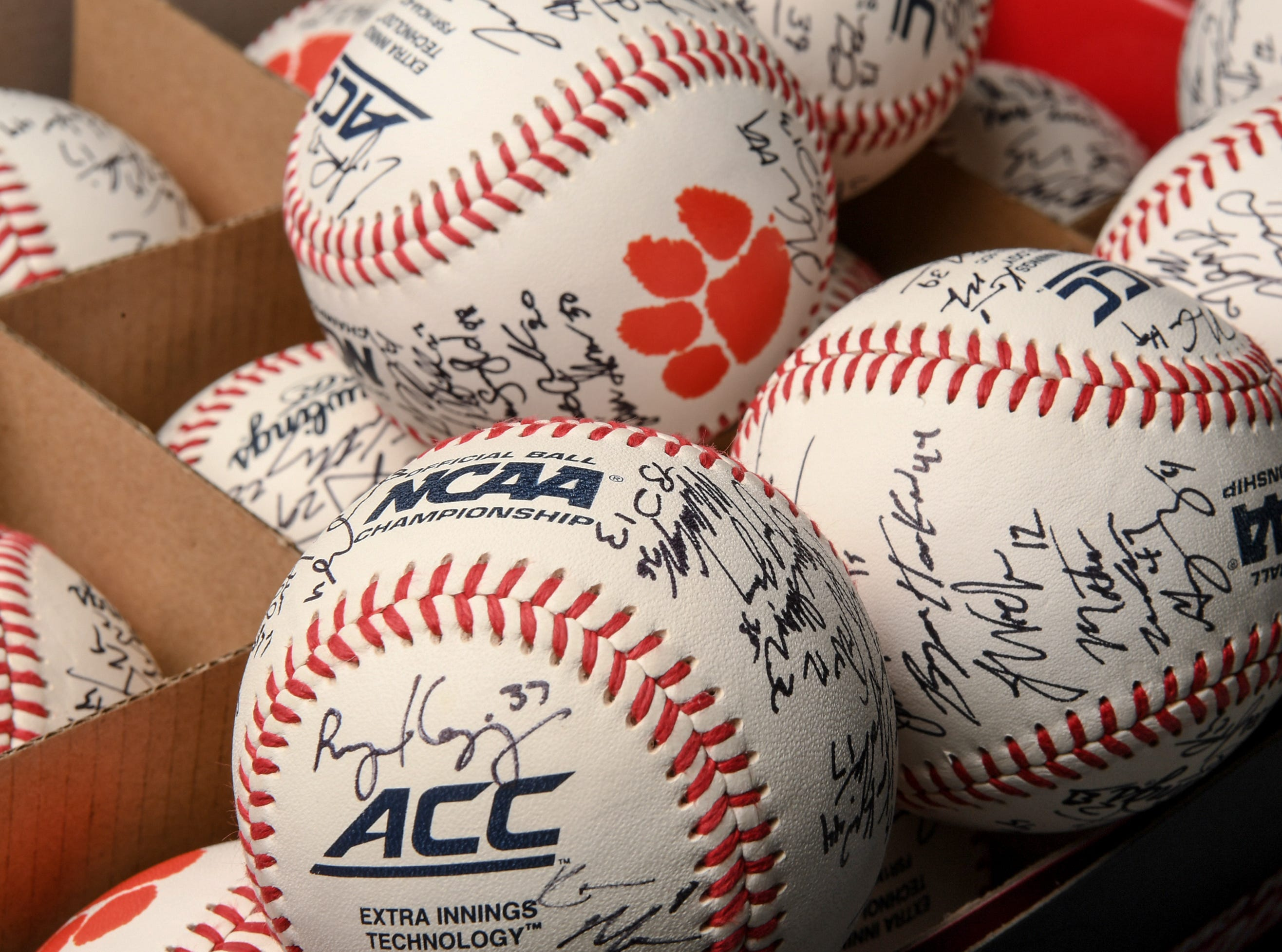 Players autographed baseballs before practice at Doug Kingsmore Stadium in Clemson Friday.