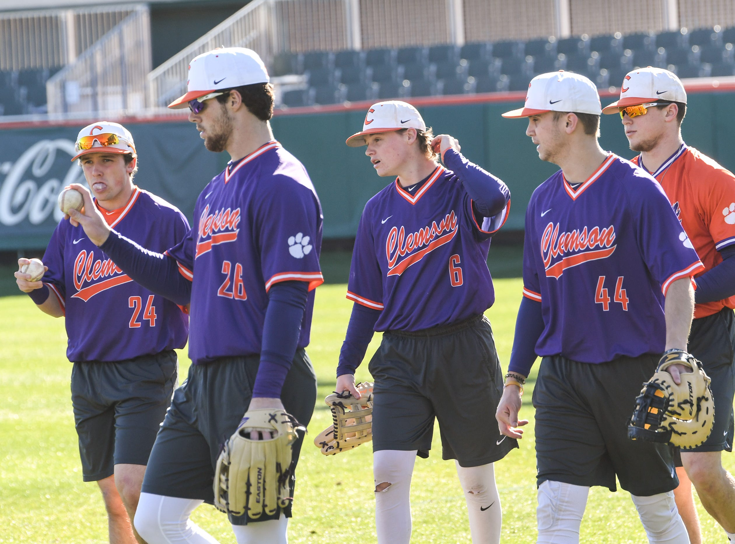 Clemson freshmen Mac Starbuck (24), left, Matt Cooper (26), Elijah Henderson (6), and Bryar Hawkins (44) warm up together during practice at Doug Kingsmore Stadium in Clemson Friday.