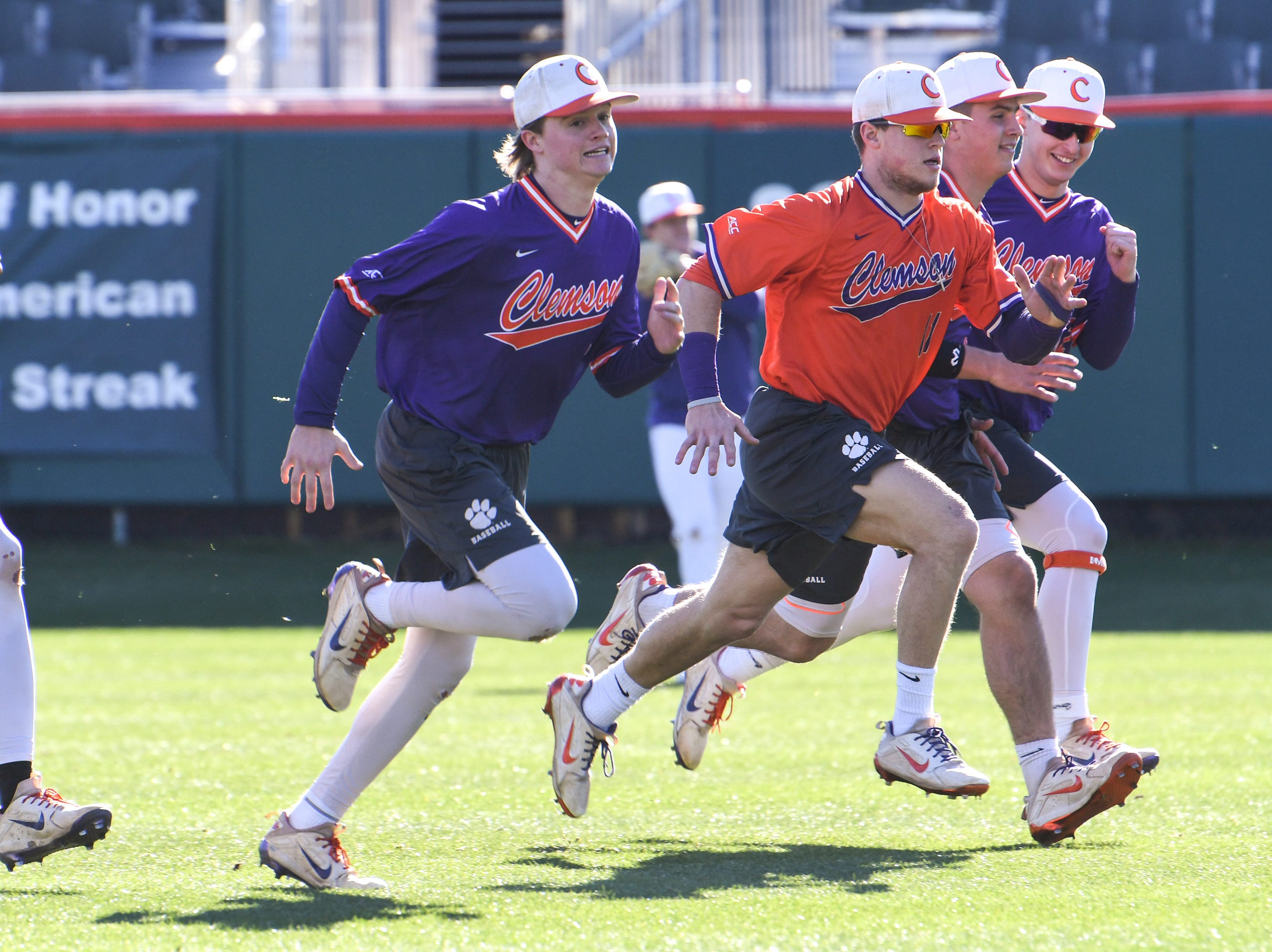 Clemson catcher Kyle Wilkie, in orange, runs with teammates during practice at Doug Kingsmore Stadium in Clemson Friday.