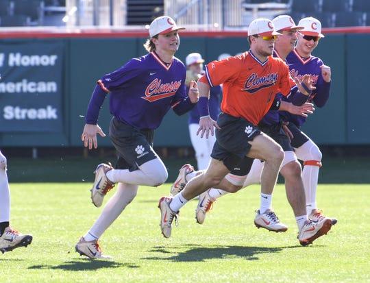 Clemson catcher Kyle Wilkie, in orange, runs with teammates during practice at Doug Kingsmore Stadium in Clemson Friday.