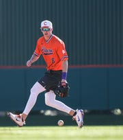 Clemson shortstop Logan Davidson (8) fields a ball to first base during practice at Doug Kingsmore Stadium in Clemson Friday.